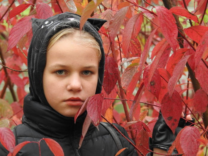 Close-up portrait of girl by autumn leaves