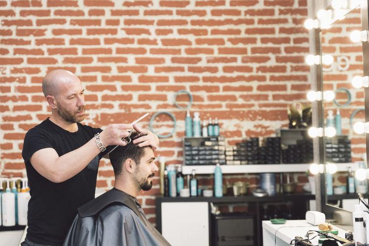 Barber cutting hair of customer in salon