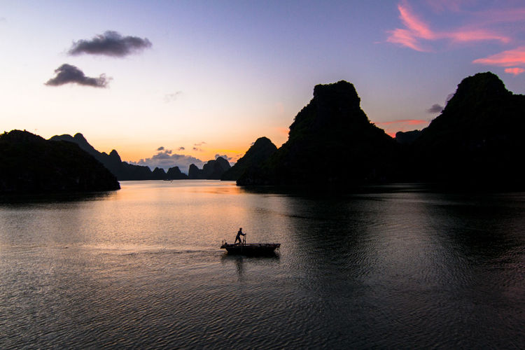 Local fisherman rowing his sampan along the beautiful ha long bay - ha long bay, vietnam