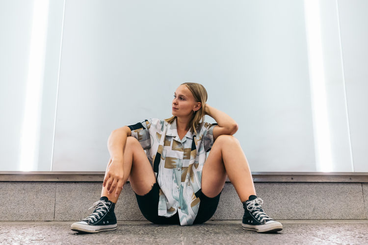 Full length of woman sitting against wall