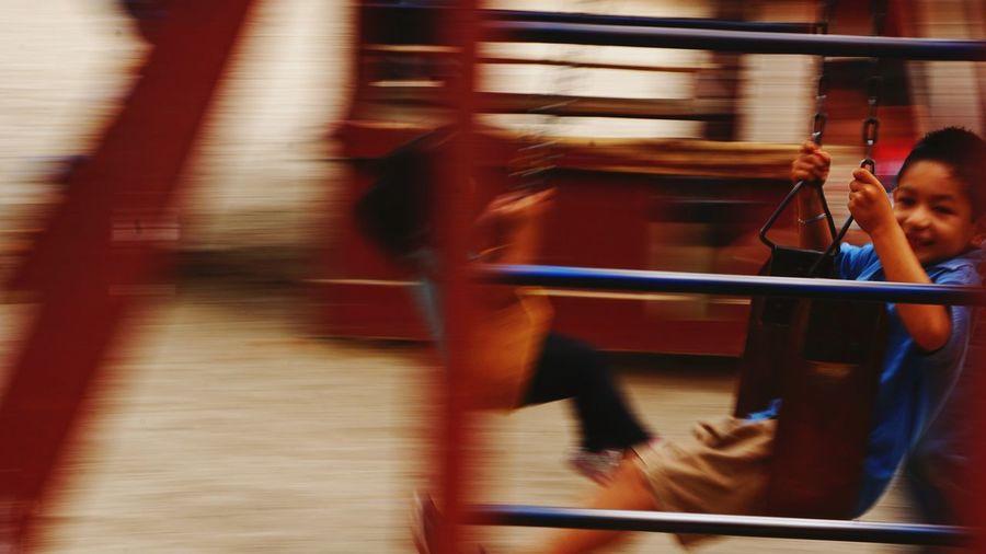 Blurred motion of happy boy enjoying swing