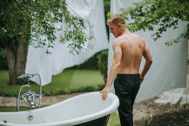 Side view of shirtless man standing in water