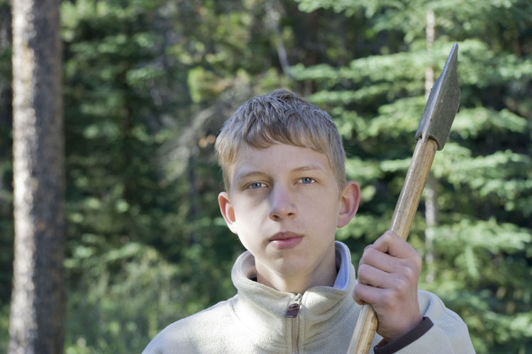 Portrait of teenage boy holding axe in forest
