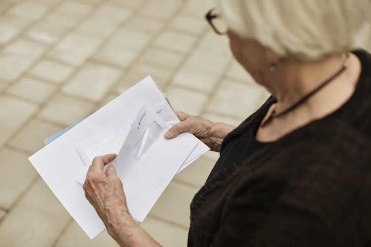 High angle view of woman with text on paper