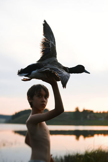 Side view of boy holding bird against sky