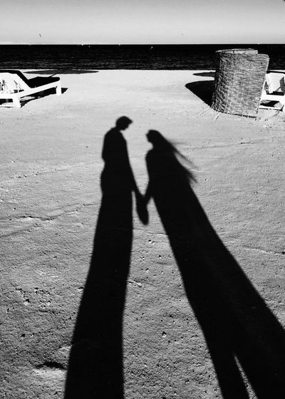 High angle view of couple shadow on sand at beach