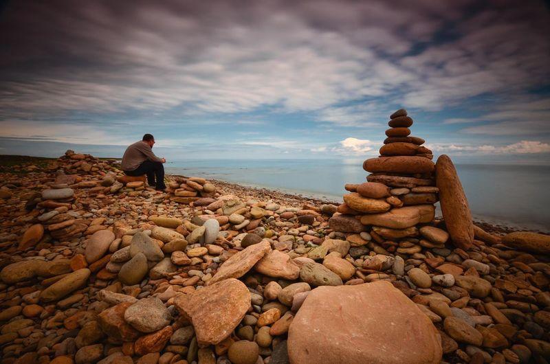 Man sitting on stone at beach