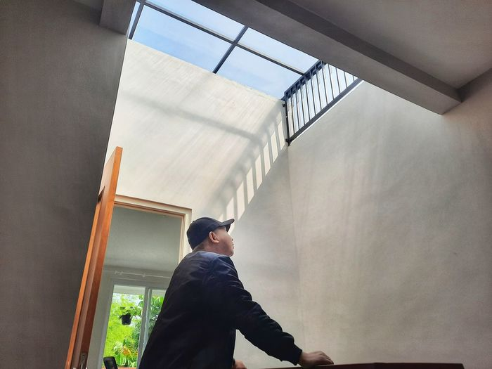 Low angle view of man looking through window