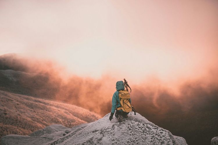 Rear View Of Hiker On Mountain Peak Against Cloudy Sky During Sunrise