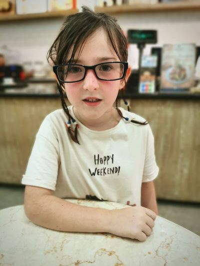 Portrait of girl wearing eyeglasses leaning on a table