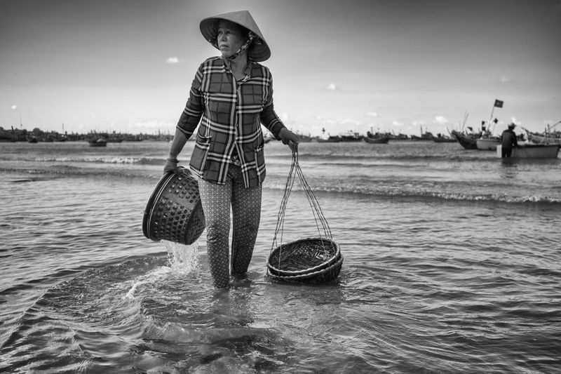 The daily activities in a fishing village in Mui Ne, Vietnam. Real People Water One Person Waterfront Standing Sky Nautical Vessel Day Men Full Length Holding Sea Nature Lifestyles Hat Leisure Activity Occupation Casual Clothing Outdoors Fishing Beach Black And White Woman