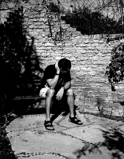 chasing harsh light in phoenix az 35mm Film Analogue Photography Arizona Birkenstock Sandals Brick Wall Background Casual Clothing Chasing Harsh Light Dark Contrasts Daytime Black And White Friday Fine Art Photography Getting Inspired Hot Weather Lifestyles Looking Away From Camera Male Model Moody Portrait Outdoors Pattern Pieces Phoenix, AZ Portrait Of A Man  Shadows On The Wall Textures And Surfaces Wearing Shorts  TakeoverContrast