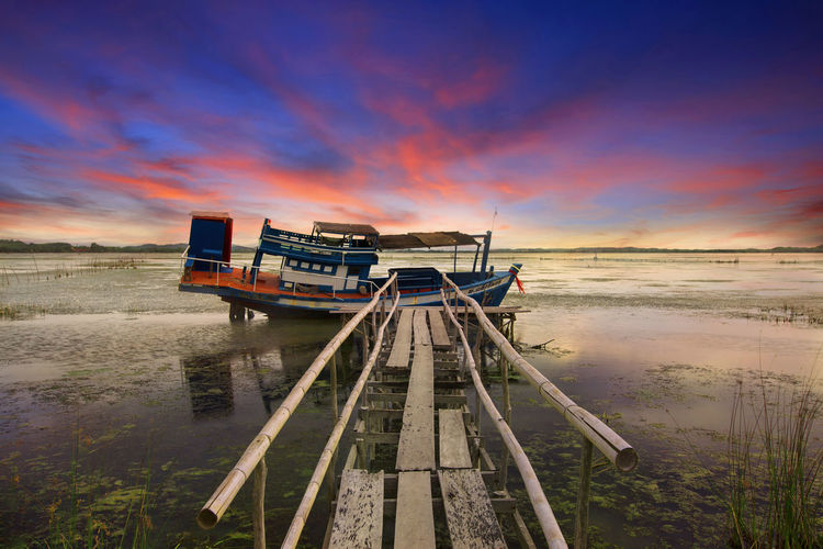 small blue wooden traditional fishing boat anchored in a natural harbor Pier Sunset_collection Thailand Wreck Architecture Beauty In Nature Built Structure Cloud - Sky Day Fishing Boat Horizon Over Water Landscape Nature No People Outdoors Scenics Sea Sky Sunrise Sunset Tranquility Travel Destinations Tree Water Wood - Material