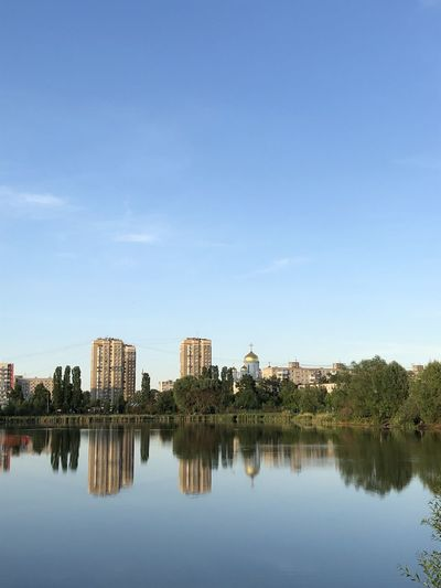 Reflection of buildings and trees in lake against blue sky