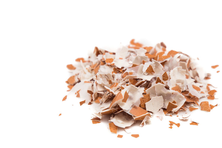 Close up of eggshell that is broken into small pieces. Eggshell are good source of calcium. Calcium Close-up Copy Space Eggshell Food Food And Drink Heap High Angle View No People Recycled Materials Shavings Still Life Studio Shot White Background White Color