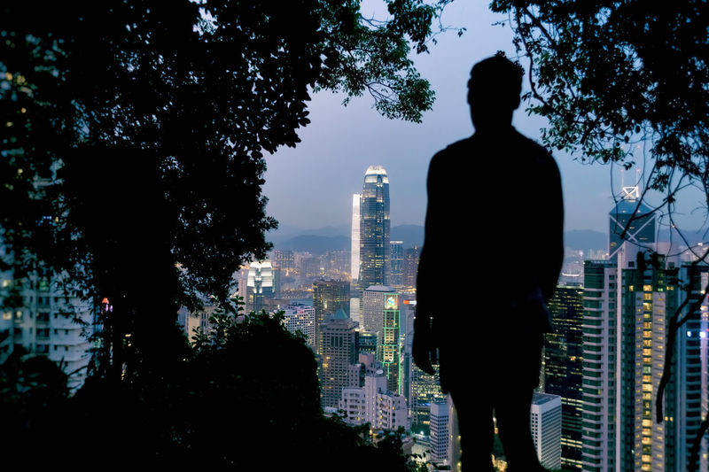 Hong Kong, China - 6 April 2015: Silhouette of a man looking at Hong Kong Skyline from Victoria Peak Adult Adults Only Architecture Business Business Finance And Industry Businessman City Cityscape Hk Hong Kong HongKong Illuminated Men Modern Night One Man Only One Person Only Men Outdoors People Silhouette Sky Skyscraper Tree Urban Skyline