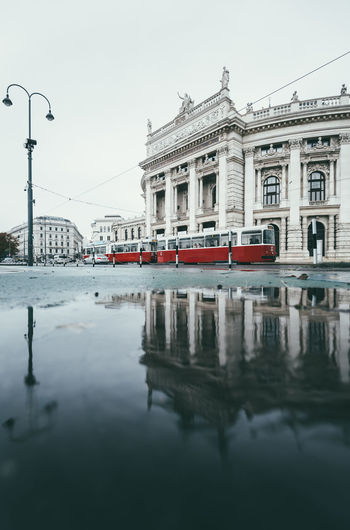 Tramway Moving By Reflection Of Building In River