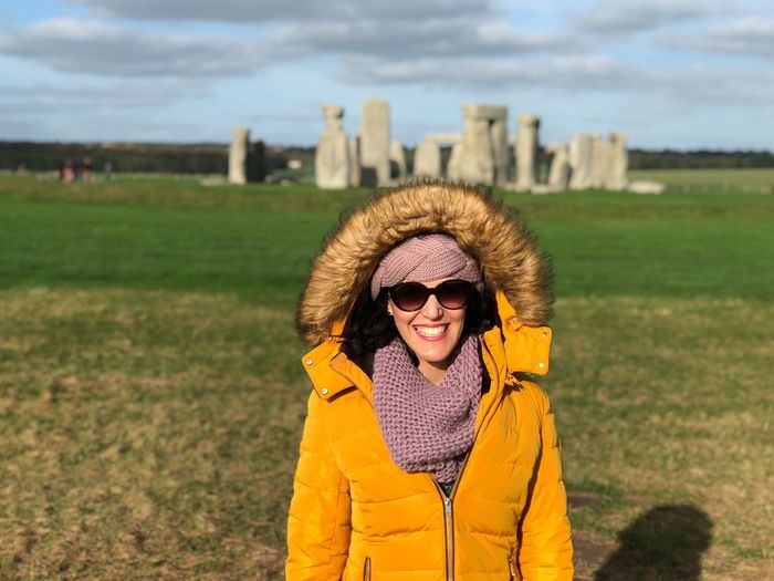 Smiling young woman standing against stonehenge