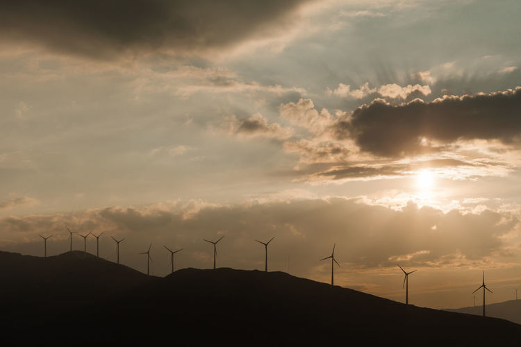 Windmills on silhouette mountain against sky during sunset