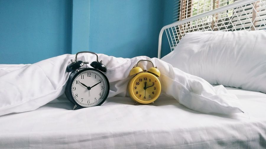 Alarm clocks on bed at home