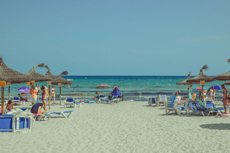 Sky Sea Water Beach Land Horizon Over Water Clear Sky Sand Nature Outdoors Parasols Beach Photography Trip Vacations Holiday Horizon Group Of People Real People Chair Summer Scenics - Nature Leisure Activity Copy Space