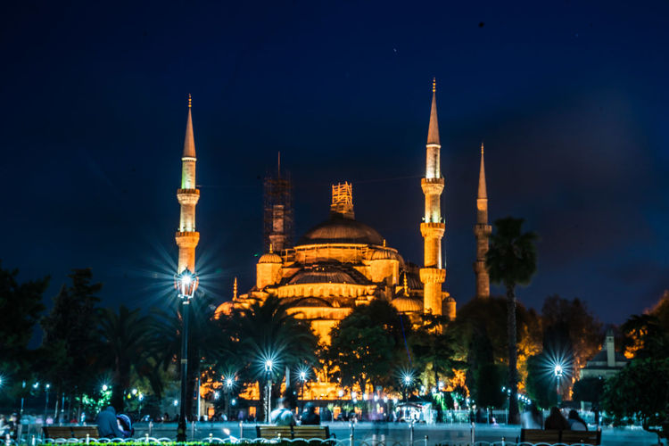 Mosque against sky in city at night