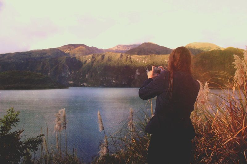 Rear View Of Woman Photographing Lake And Mountains Through Phone