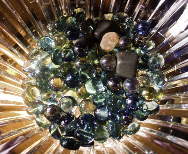 A crystal bowl containing marbles and stones, sunlight is shining and reflecting off these marbles and shiny stones. The light reflects and moves through the glass and the marble, creating an interesting sparkling effect. Bowl Of Marbles Close-up Crystal Bowl Glass Bowl Glass Bowl Of Marbles Indoors  Large Group Of Objects Marbles No People Shine Shine Bright Shiny