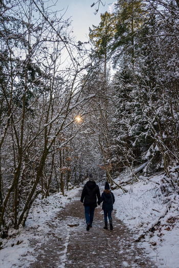 Rear view of women walking on snow covered tree