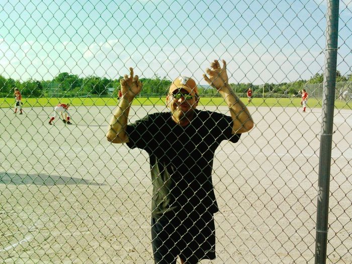 Rear view of man playing with chainlink fence