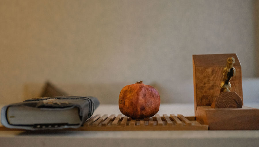 Close-up of apples on table against wall