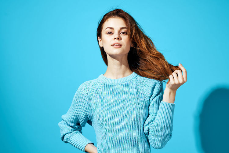 Beautiful woman standing against blue background