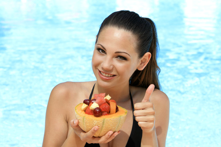 Portrait of smiling woman with fruits gesturing against swimming pool