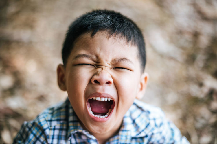 Close-up portrait of cute boy yawning while standing outdoors
