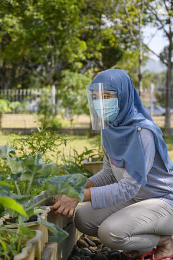 A hijab woman is wearing masker and face shield while gardening in covid 19 pandemic situation