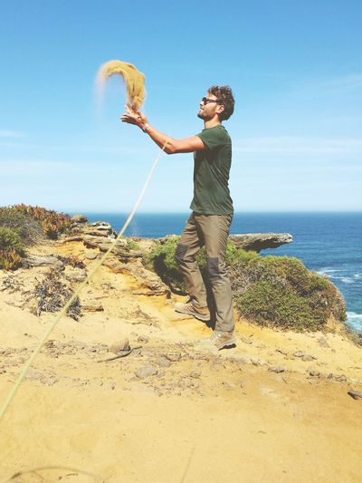 Man throwing sand at beach