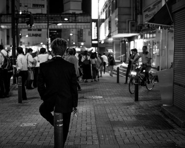 People walking on footpath at night