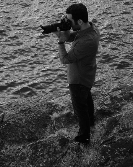 Side View Of Man Photographing While Standing On Rock By Sea