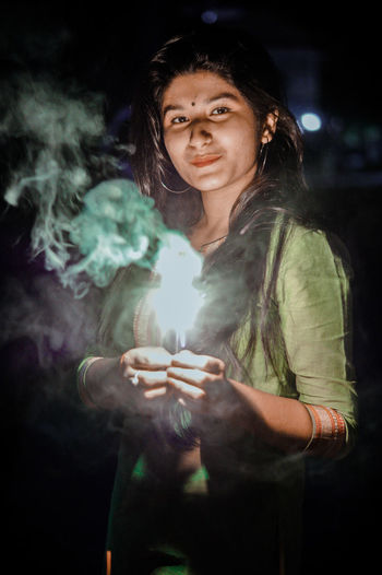 Portrait of beautiful young woman holding illuminated sparkler while standing at night