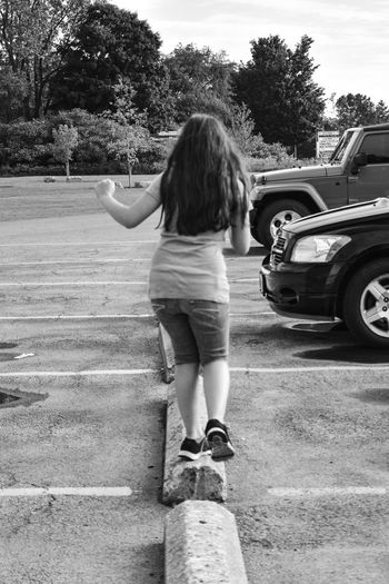 rear view of girl balancing on parking blocks Balancing Act Casual Clothing Child Playing Childhood Day Full Length Girls Leisure Activity Lifestyles Long Hair On Young Girl One Person Outdoors People Physical Activity Real People Rear View Road Sky Standing Transportation Tree The Street Photographer - 2017 EyeEm Awards Streetphotography Street Photography