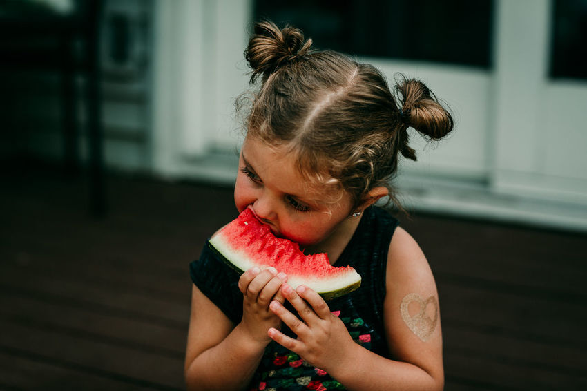 Pigtails  Casual Clothing Childhood Close-up Day Eating Fake Tatoo Focus On Foreground Food Food And Drink Freshness Front View Fruit Girls Healthy Eating Healthy Lifestyle Holding Juicy Leisure Activity Lifestyles One Person Outdoors Real People SLICE Watermelon Fresh On Market 2017