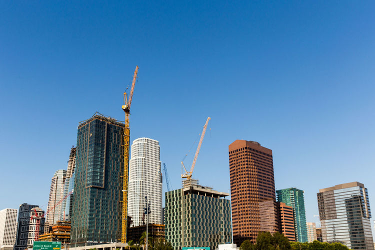 Low Angle View Of Cranes And Incomplete Buildings