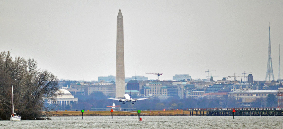 Washington DC Skyline with Washington Monument and airplane landing City Skylines Potomac River Washington DC Washington DC Washington Monument Washington, DC Skyline Airplane Architecture Building Exterior Built Structure Travel Destinations Travel Destinations Outdoors Relaxation Water