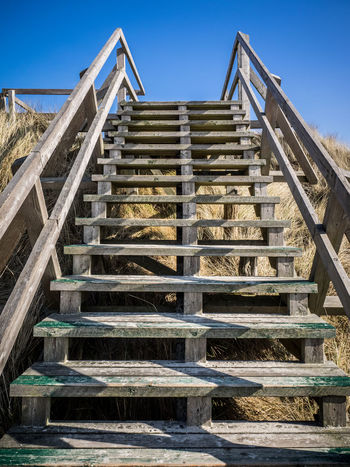 Stairway right into the blue sky (Himmelsleiter) Amrum Holz Architecture Built Structure Clear Sky Climbing Day Going Up Hand Rail Himmelsleiter Low Angle View No People Nordsee North Sea Outdoors Railing Sky Staircase Stairs Steps Steps And Staircases Stufen Treppe Upstairs Wood - Material