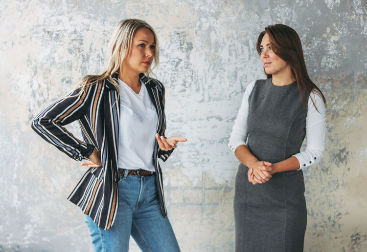 Woman discussing with colleague against wall