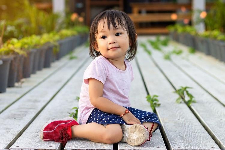 Baby girl sitting on footpath