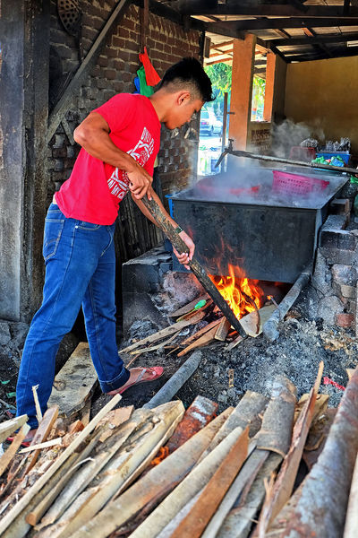 Seberang Takir, Terangganu - April 4th, 2017: A man firing the hot bath using the pile of timber. The hot bath is use to steam raw fish to make keropok lekor Adult Adults Only Barbecue Burning Day Editorial  Flame Food Full Length Heat - Temperature Lekor Mammal Men Metal Industry Mid Adult One Man Only One Person Only Men Outdoors People Preparation  Real People Terengganu