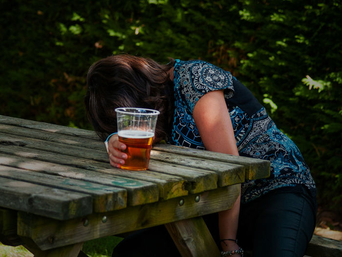 Woman having beer while sitting at table in yard