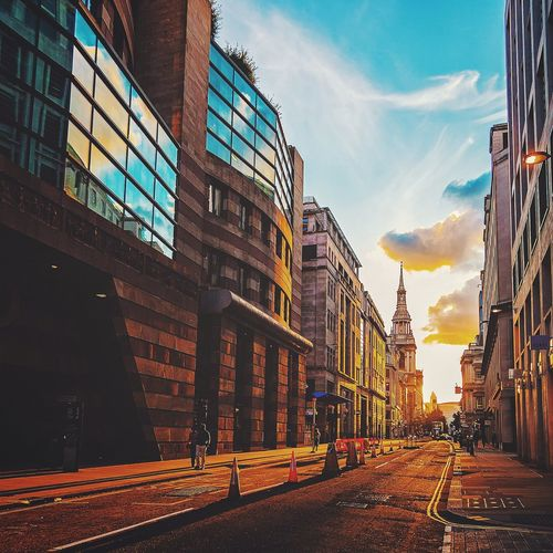 Street amidst buildings in city during sunset