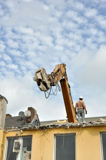 Low angle view of man standing on roof by crane against cloudy sky